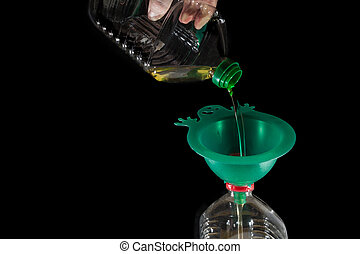 funnel - old frying oil pouring into another bottle with a...