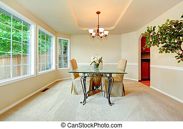 Luxury dining room with french window, ivory walls with...
