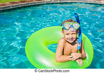 Young Kid Having Fun in the Swimming Pool On Inner Tube Raft...