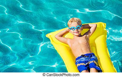 Boy Relaxing and Having Fun in Swimming Pool on Yellow Raft...