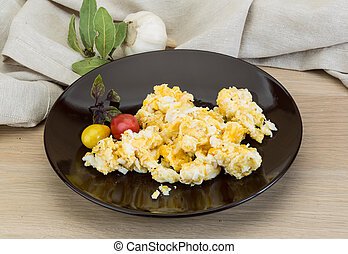 Scramble with tomato on the wooden background