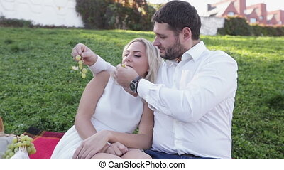 Couple on picnic eating grapes