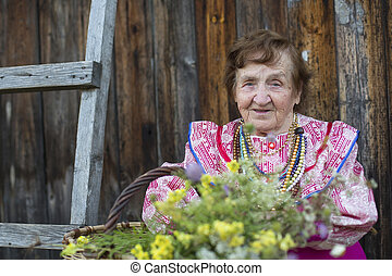 Old woman outdoors in the countryside.