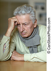 Portrait of an elderly man with a headache on a beige...