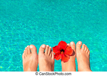 macro picture the newlyweds feet by the pool with flower