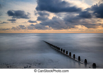 Beautiful long exposure vibrant concept image of ocean at sunset