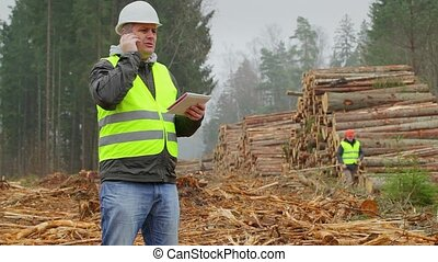 Lumberjack with tablet PC and cell phone in forest