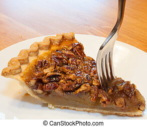 Dive in - Fork going into a piece of pecan pie on a white...