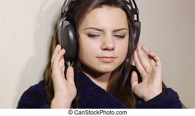 Girl bathrobe in headphones - Seated in the headphones and a...