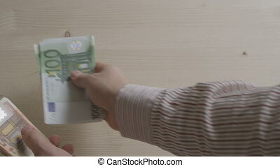 person counting euro bills - hands of businessman counting...