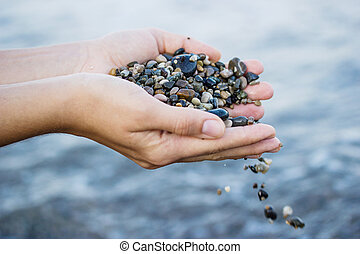 A girl plays with sea stones on the seashore