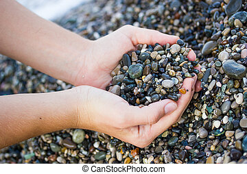 The girl is holding a sea stones - The girl on the beach...