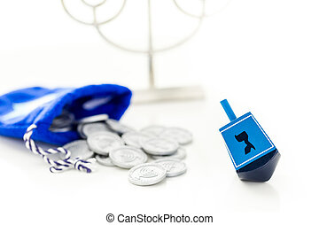 Hanukkah - Blue dreidel with silver tokens on a white...