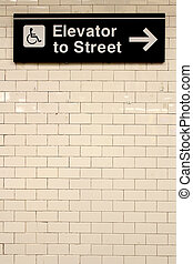 New York City Station subway directional sign on tile wall....