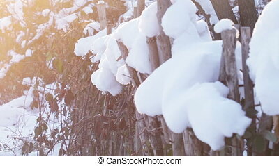Wooden fence under snow - In backlit sunshine wooden fence...