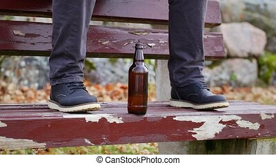 Beer bottle at a man's legs
