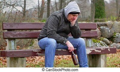 Sorrowful man with beer bottle on the bench
