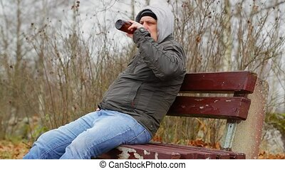 Man with beer bottle on the bench
