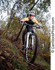 Cyclist downhill in a forest outdoors. He is practicing...