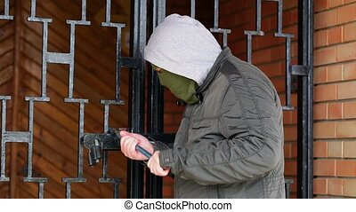 Robber in mask with crowbar try to open gates