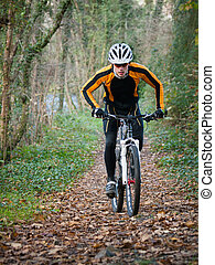 Cyclist on a mountain bike riding in the forest outdoors.