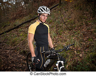 Cyclist in the forest standing and looking at camera