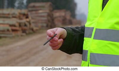 Worker with cigarette near piles of logs in forest
