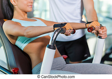 Training with instructor. Close-up of beautiful young woman working out in gym while instructor supporting her