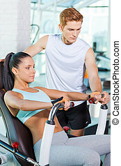 Helping her with exercising. Beautiful young woman working out in gym while confident instructor helping her