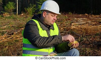 Lumberjack eating potato chips in the forest