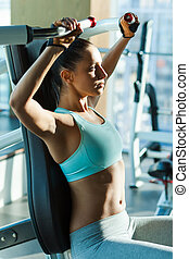 Sports training in gym. Attractive young woman looking concentrated while working out in gym