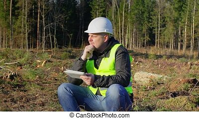 Lucky forest engineer with tablet PC in the forest