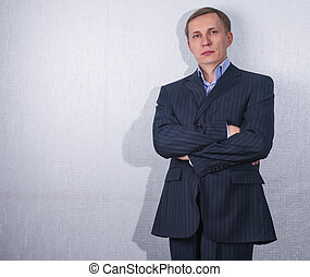 Portrait of a handsome young man in a business suit against...