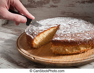 Cutting a piece of sponge cake with a knife.
