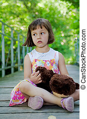 5 years old girl on the bridge with teddy bear