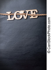 carved wooden letters love on a black background