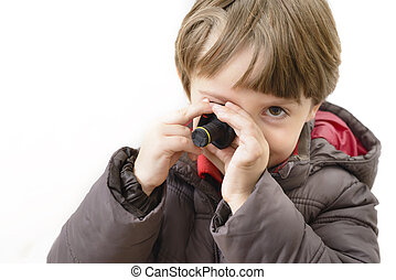 Cute boy playing with miniature camera isolated on white