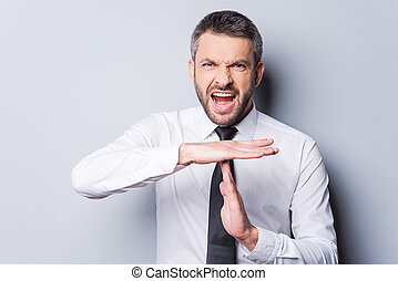 Time out! Furious mature man in shirt and tie shouting and...