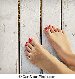 Womens feet on the boards of the pier - Womens feet in the...