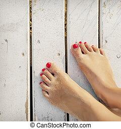 Women's feet on the boards of the pier - Women's feet in the...