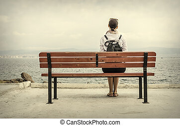 Woman sitting on bench - Lonely woman sitting on a bench by...