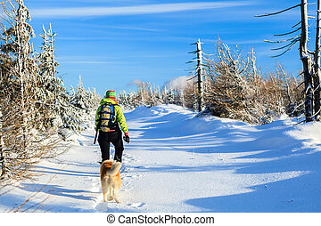 Woman hiking with dog in winter