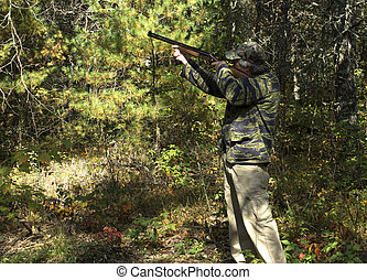 Autumn hunter - Hunter in the Autumn woods aiming at an...