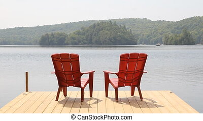 Two red chairs on cottage dock.