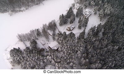 View from above of winter forest and house on edge