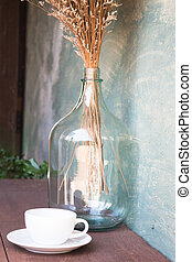 Coffee cup and dried flower vase on wooden table, stock...