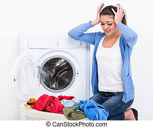 Washing - Tired housewife is doing laundry with washing...