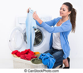 Washing - Happy young woman is doing laundry with washing...