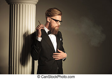 man looking down while holding a cigarette in his hand -...