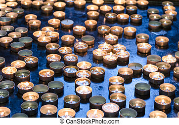 Candles donation in a church in memory of the survivors